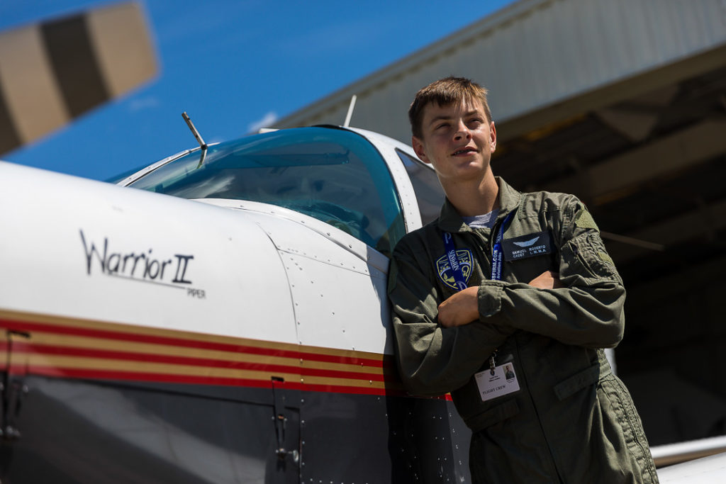 young flight crew cadet next to airplane