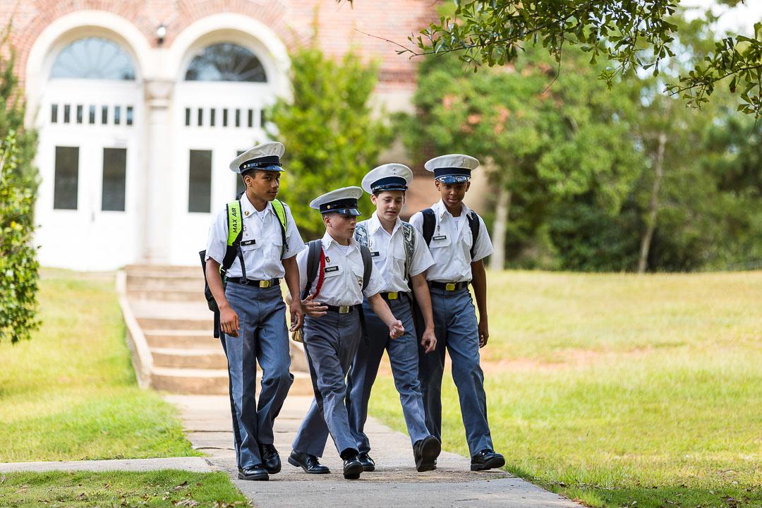 four boys wearing backpacks
