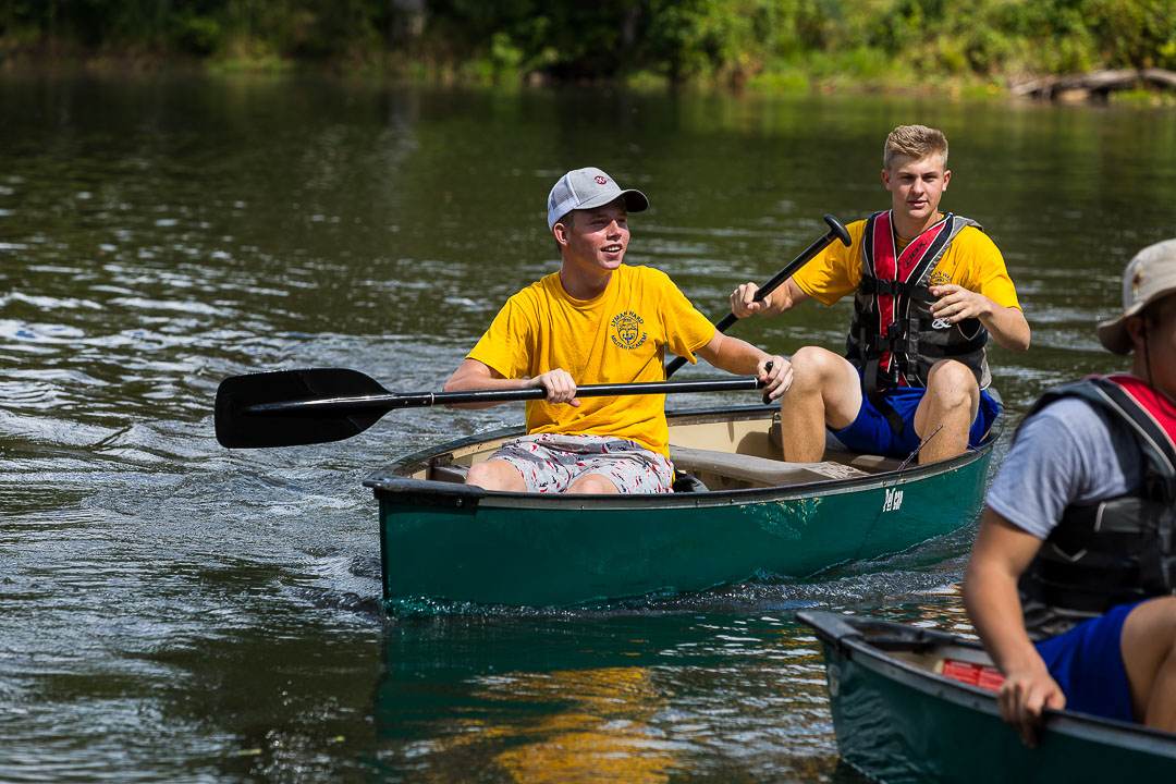 boys padding in canoes
