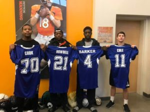 four cadets holding sports jerseys